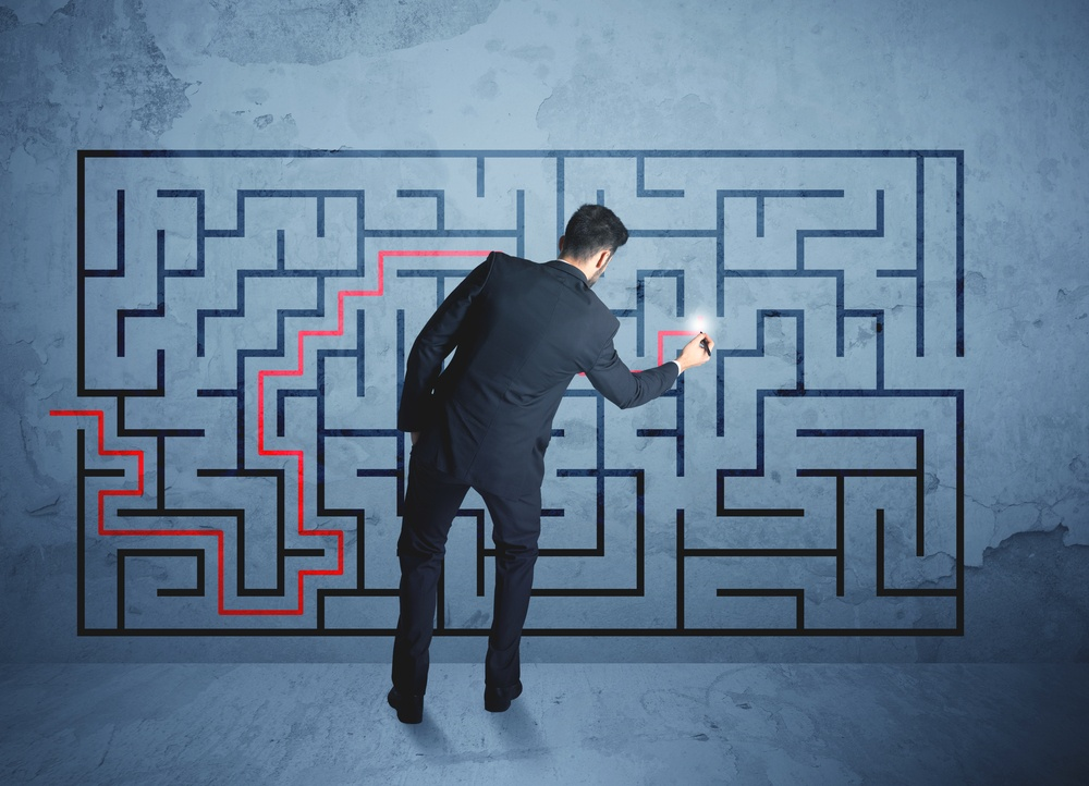 Businessman finding the solution of a maze